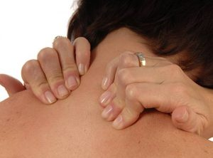 women with back and neck ache rubbing both shoulders isolated on white