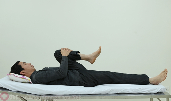 Nằm trên giường, dùng tay kéo một chân lên