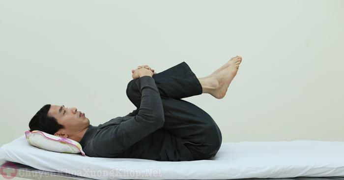 Nằm trên giường, dùng hai tay chéo đầu gối